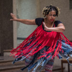 Dancer/choreographer Andréa Spearman in motion with red fringe top and blue fringed bottoms splaying with her movement