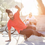 Man in red shirt with topknot breakdancing in urban setting, sun highlighting him