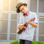 Young Asian man with glasses wearing fedora and headphones around neck playing small guitar