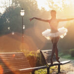 Ballet dancer in white tutu standing en pointe on top of a park bench, arms spread wide and sun highlighting the tutu