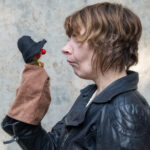 Handpuppet with red nose sticking out from under rounded hat faces off with woman with short hair, who is puckering her mouth