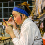 Asian woman applying makeup for Chinese Opera