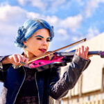 young woman with blue hair playing pink violin under blue sky with puffy clouds
