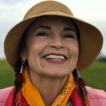 Indigenous woman with bright smile, straw hat and orange bandana around neck smiles confidently to right side of camera